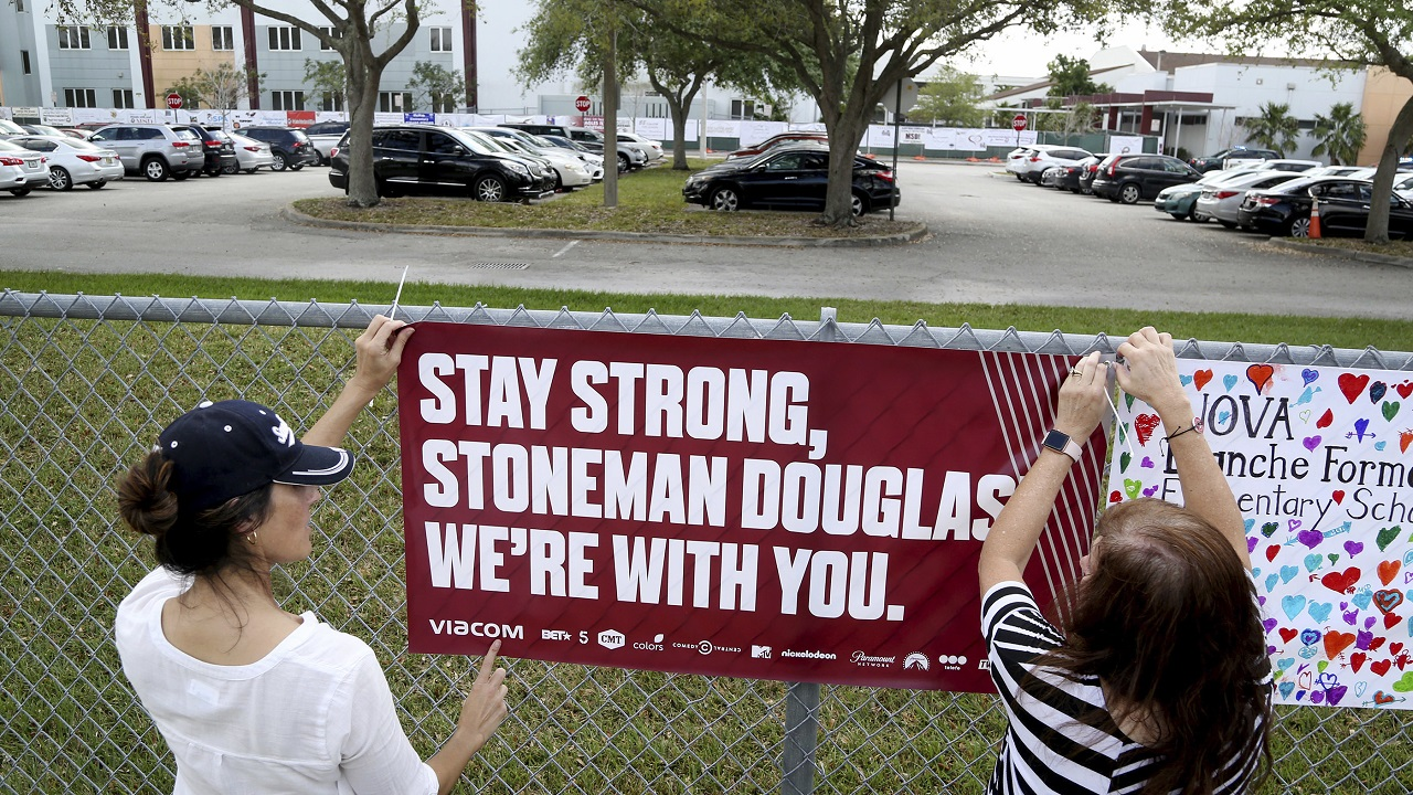 (Image: AP: Volunteers hang a banner at the high school in Florida to welcome returning student)