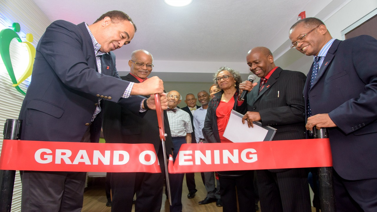 Health Minister, Dr Christopher Tufton (left foreground), doing ribbon-cutting duties at Thursday's grand opening ceremony for the new full-service cardiac care facility at Medical Associates Hospital in St Andrew. Other national and medical interests share in the special occasion.