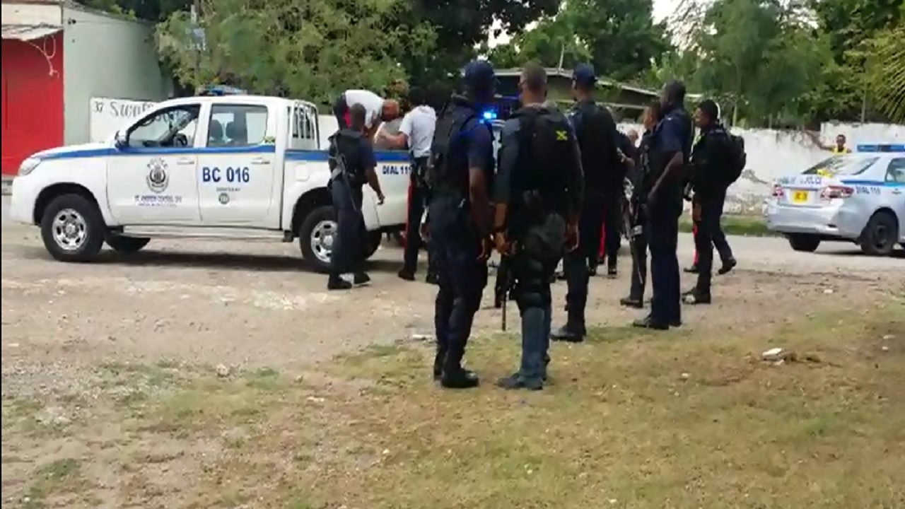 Police personnel at the scene of Friday morning's fatal shooting of a man after he reportedly attended the Stadium Police Station to report on condition of his bail.