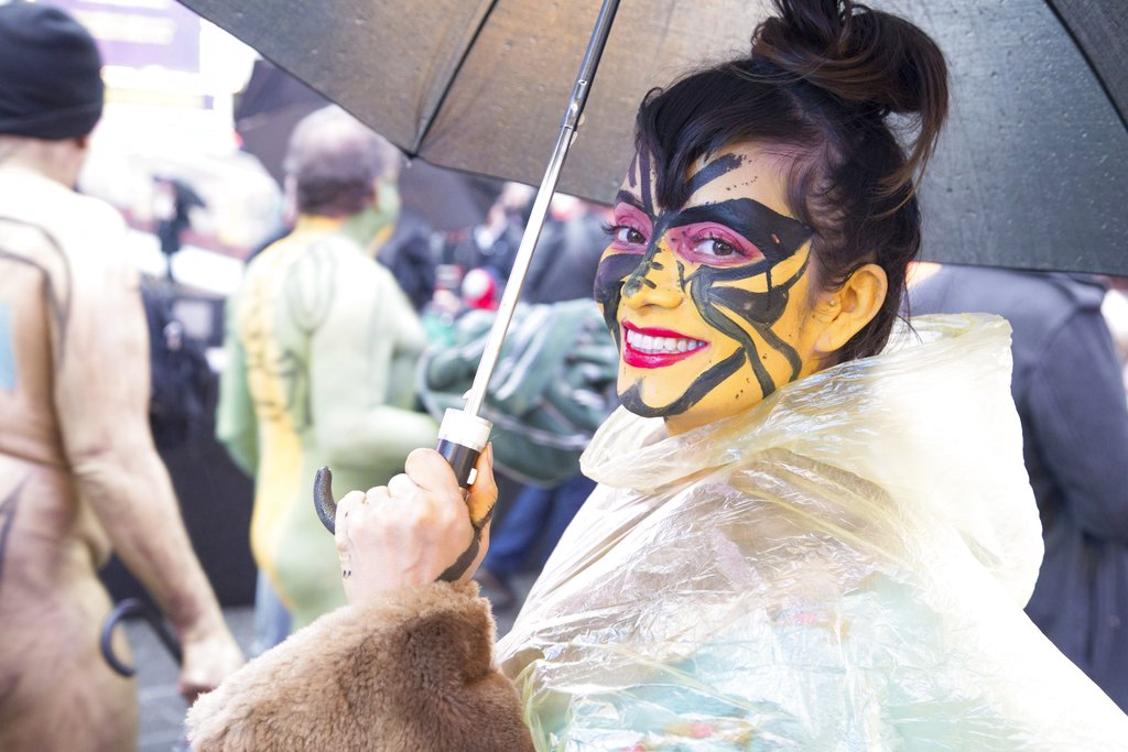 This photo provided by Andy Golub shows a nude model in a see-through poncho poses with her umbrella in the rain and cold during the Polar Bear Paint body-painting event in New York City's Times Square. (Andy Golub via AP)