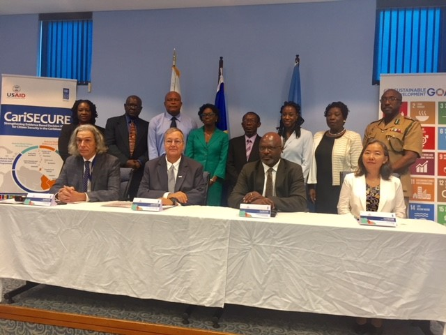 Participants pose for a photo after the CariSECURE launch. Seated from left to right are: Paolo del Mistro, Team Leader, CariSECURE project; Chris Cushing, Mission Director, USAID/Eastern and Southern Caribbean; Adriel Brathwaite, Attorney General of Barbados; and Chisa Mikani, UNDP Deputy Resident Representative for Barbados and the OECS.