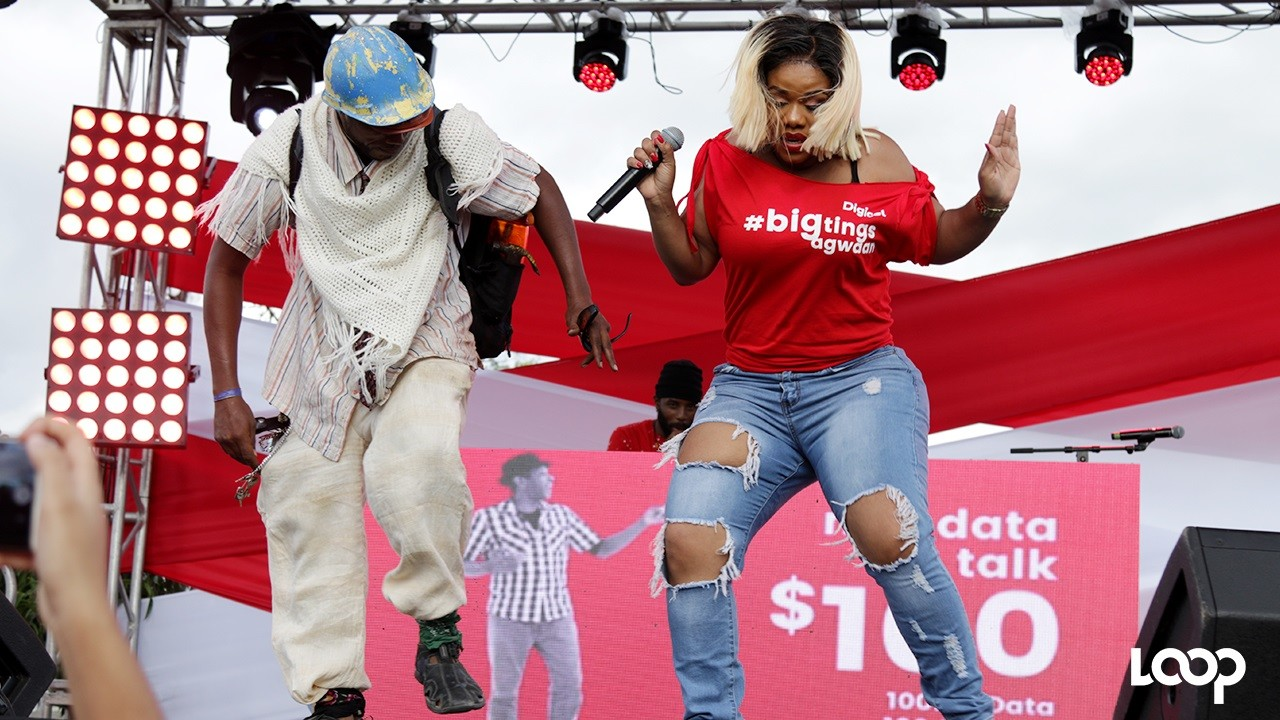 A Digicel customer joins the  'Fluffy Diva', Miss Kitty, on stage to bust a move during the company's Destination Data stop at Mandela Park on Wednesday.  (PHOTOS: Richard Baker)