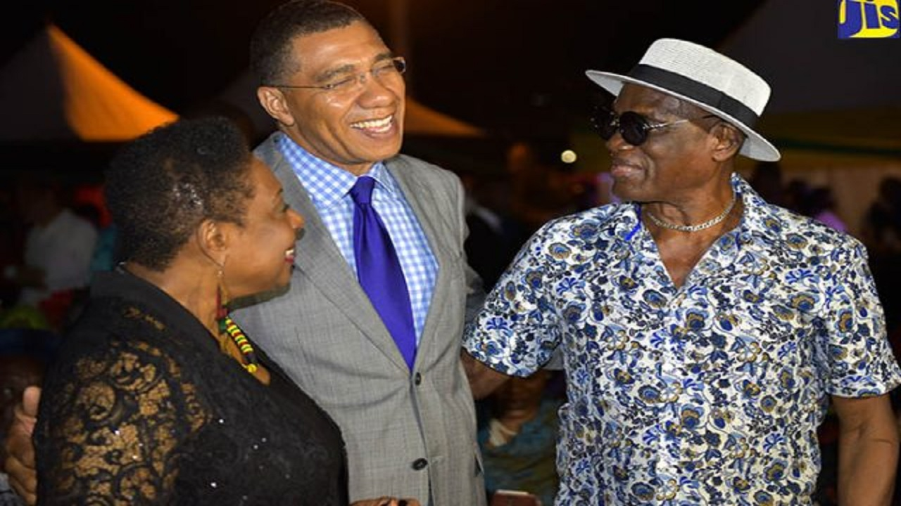 Prime Minister Andrew Holness (centre), exchanges pleasantries with Minister of Culture, Gender, Entertainment and Sport, Olivia Grange (left); and record producer, Winston 'Niney' Holness, during a Reggae Month reception on the lawns of Jamaica House on February 20. (PHOTO: JIS)