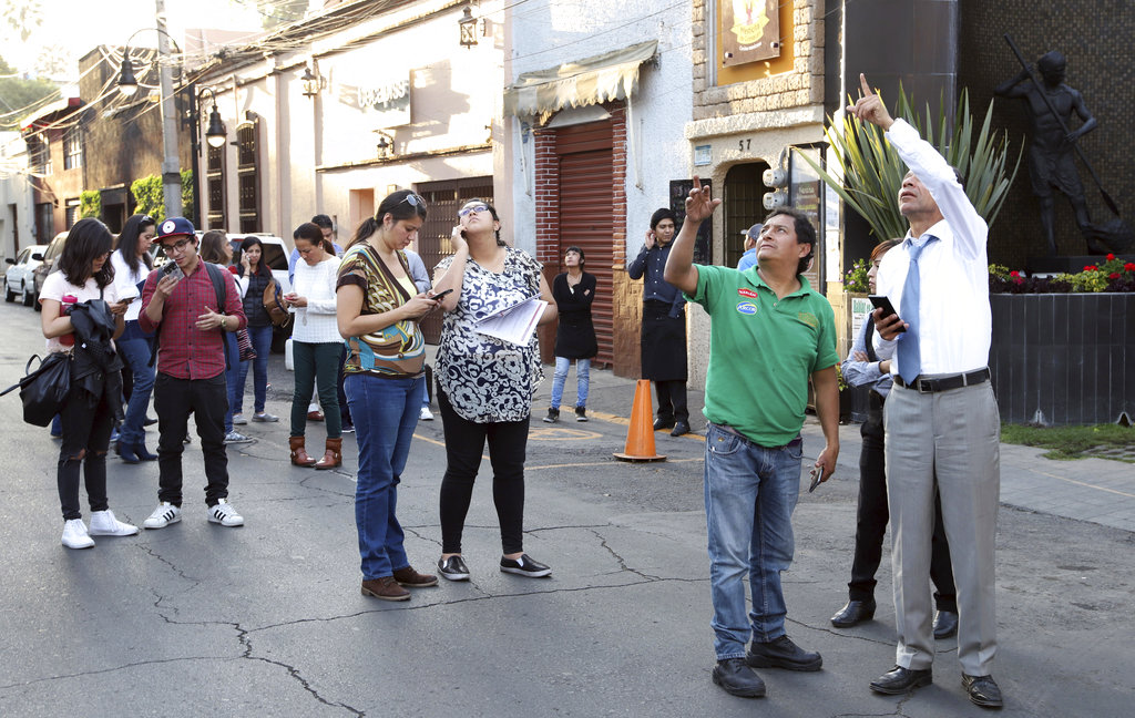 People stands in the street as an earthquake shakes Mexico City, Friday, Feb. 16, 2018. (AP Photo/Bernandino Hernandez)
