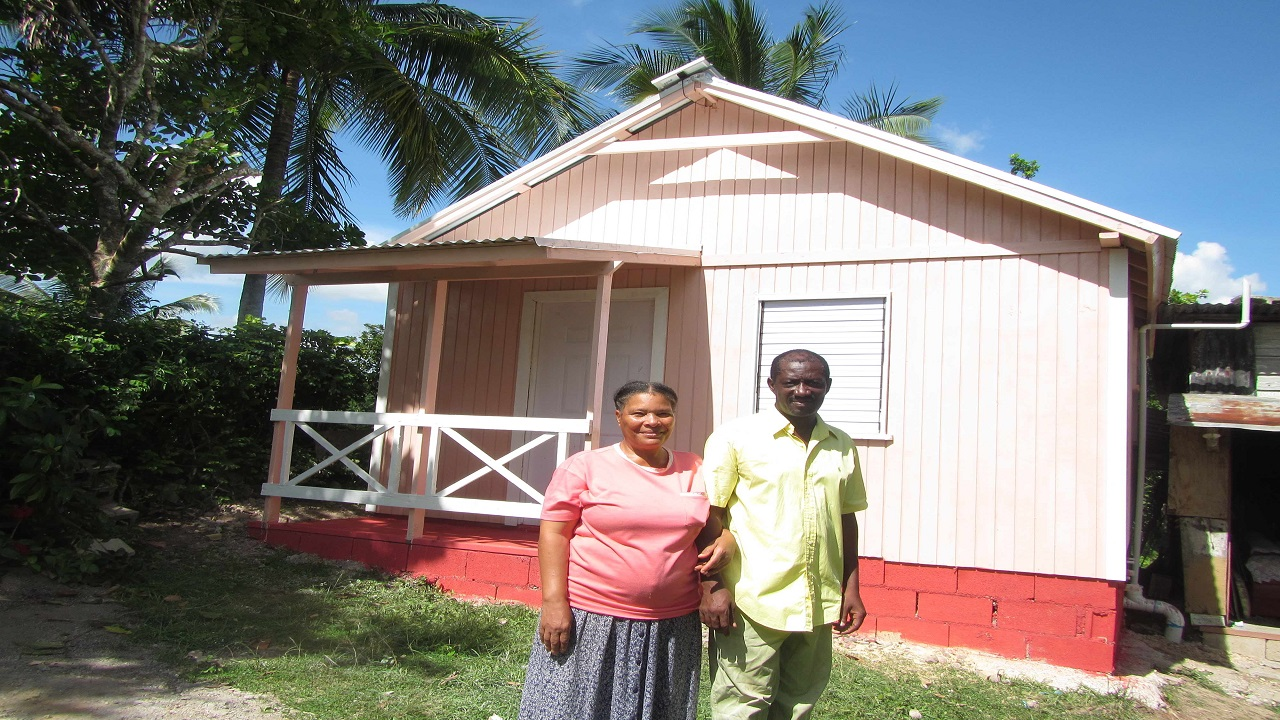 Food for the Poor Housing beneficiary, Calvin Walters stands with his wife Hazel in front of their new home in Pennants, Clarendon.
