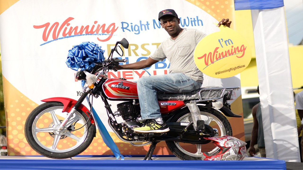 Everald Morgan, the second winner of a Wassy Motorcycle in the First Global MoneyLink 'Winning Right Now' Christmas promotion, lets the world know he's winning as he sits atop his new bike.