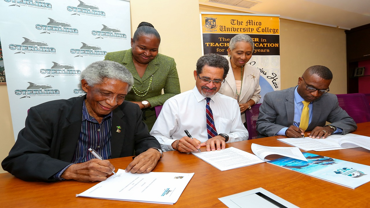Chief Education Officer Dr. Grace McLean (standing left) bears witness to the signing of the MOU with (from left) pro-chancellor of The Mico University College Neville Ying, CEO and President of Sterling Asset Management Charles Ross and Principal of The Mico University College, Dr. Asburn Pinnock. Also looking on is Sharon Bogues - Wolfe, Director of Alumni Affairs at the Mico University College.