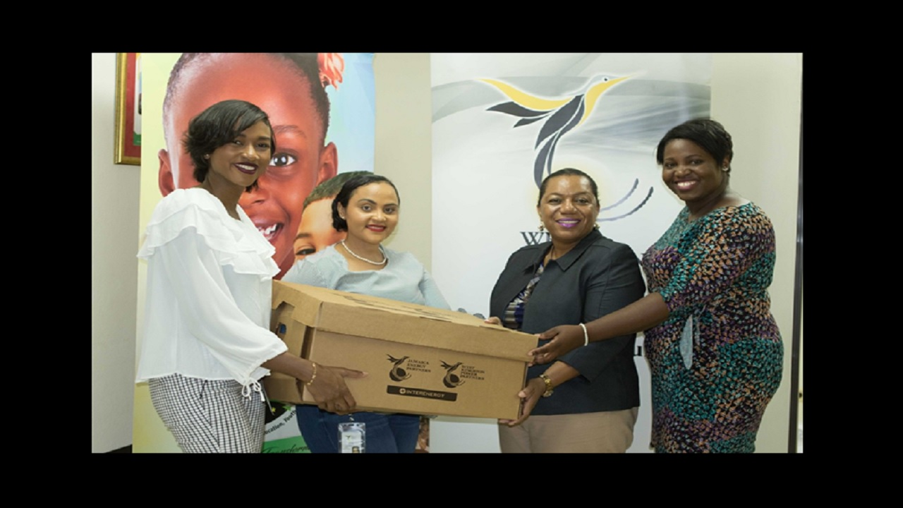 Moya-Mae Rose (left), PR & Digital Marketing Specialist at JEP and WKPP and Melissa Newman (centre-left), JEP and WKPP's Public and Community Relations Specialist hand over one of the many personal care packages for children at the Walkers' Place of Safety, to Rosalee D. Gage-Grey (centre-right), CEO of the CDA and Rochelle Dixon, CDA's PR and Communications Manager.