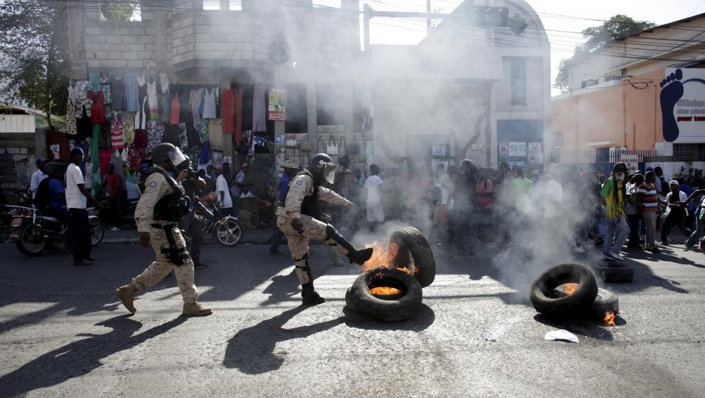 Des policiers évacuant des pneus enflammés dans une manifestation. Photo: RFI