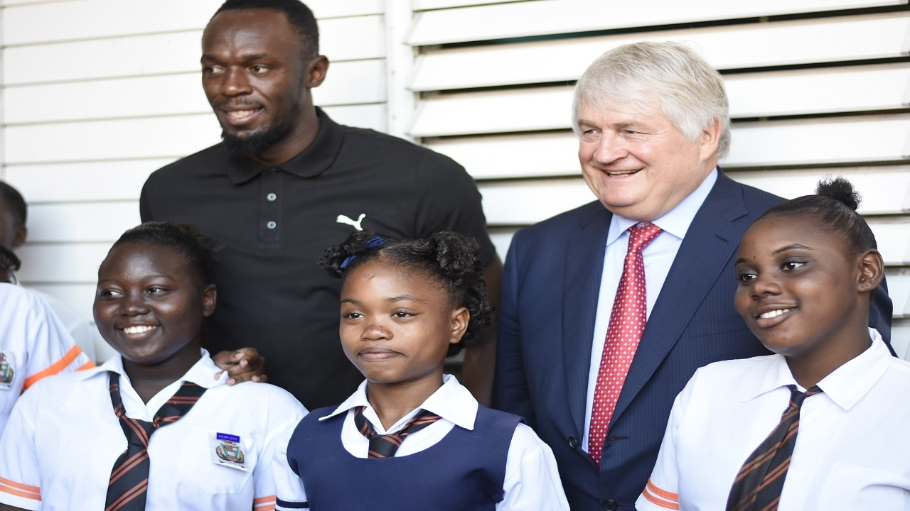 Denis O'Brien, Digicel founder and chairman (second right) and track legend Usain Bolt pose with Tivoli Gardens Comprehensive High School students on Monday. (PHOTOS: Marlon Reid)