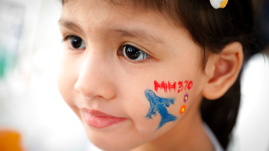 A girl has her face painted during the Day of Remembrance for MH370 event in Kuala Lumpur, Malaysia, Saturday, March 3, 2018. (AP Photo/Vincent Thian)
