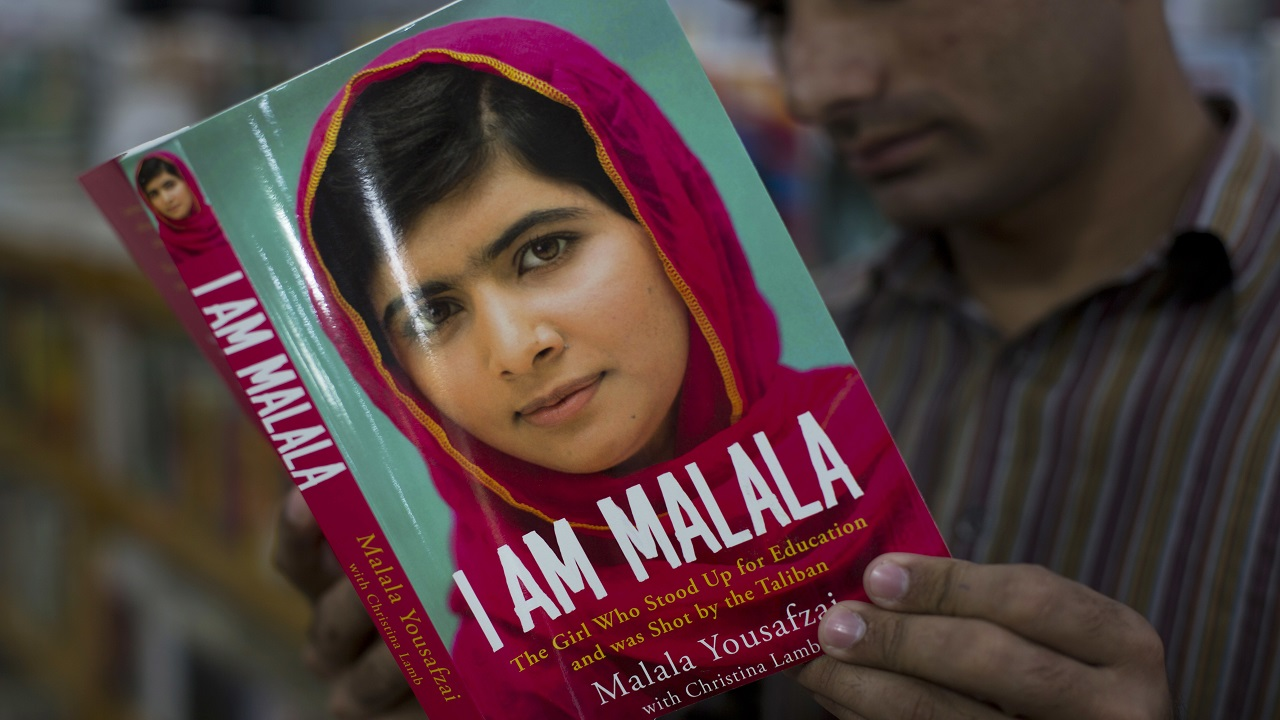(Image: AP: A man reads the book written by Malala Yousafzai in Islamabad on 10 October 2014)