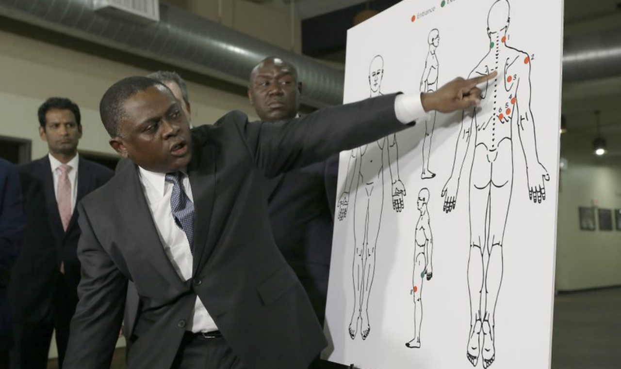 Pathologist, Bennet Omalu, gestures to a diagram showing where police shooting victim Stephon Clark was struck by bullets, during a news conference, Friday, March 30, 2018, in Sacramento, Calif. Omalu, who was hired by the family to conduct an independent autopsy, said Clark was shot seven times from behind and took up to 10 minutes to die. (AP Photo/Rich Pedroncelli)