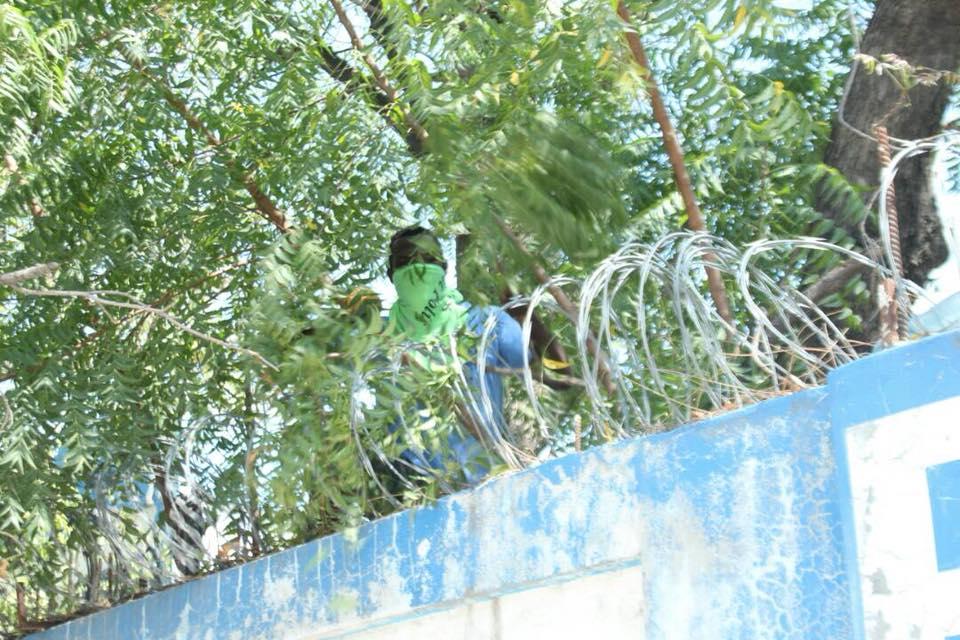 Un agent de la PNH en train de faire une retouche de peinture sur le mur d'un commissariat. Photo: Police Nationale d'Haiti - PNH (Facebook)