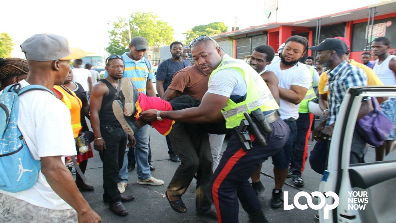 A police officer and other first responders carry one of the injured men to a waiting motor vehicle. (PHOTOS: Llewellyn Wynter)