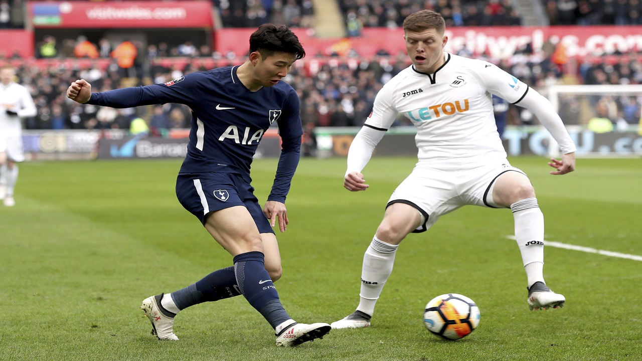 Tottenham Son Heung-Min, left, and Swansea City's Alfie Mawson battle for the ball during the English FA Cup, quarterfinal football match at the Liberty Stadium, Swansea, Wales, Saturday March 17, 2018.