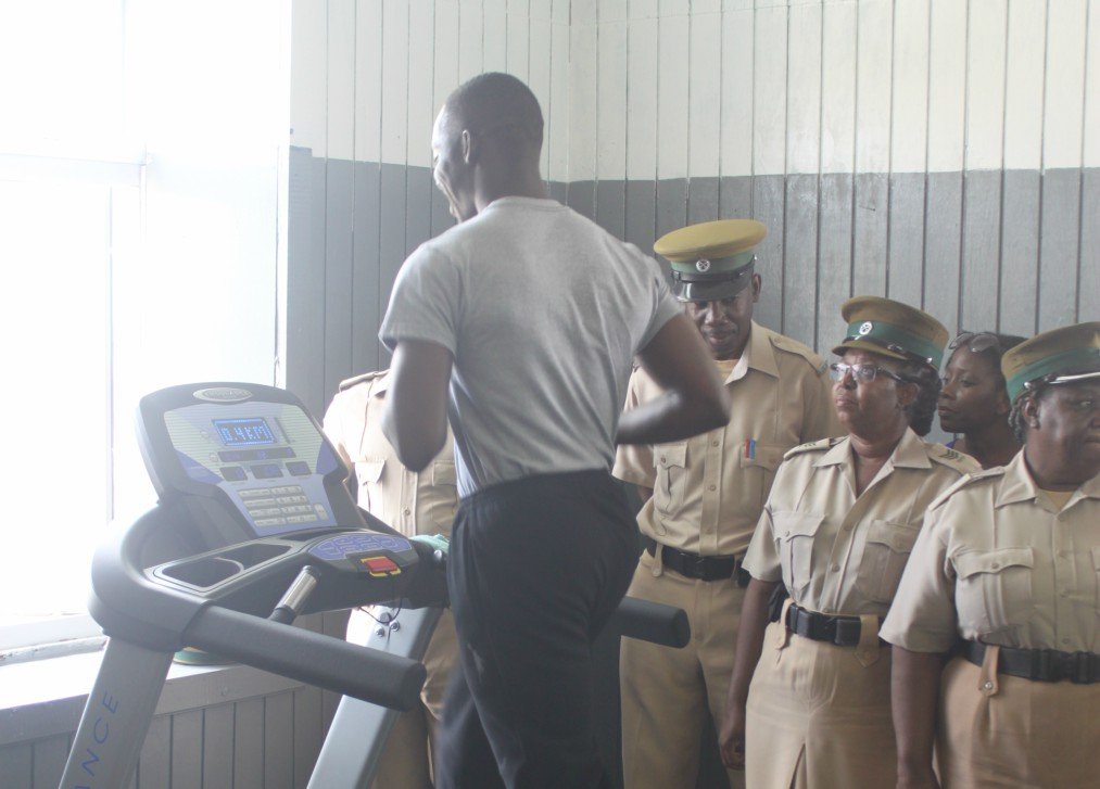 Prison officer, Damian Headley running on the treadmill while his fellow officers observe.