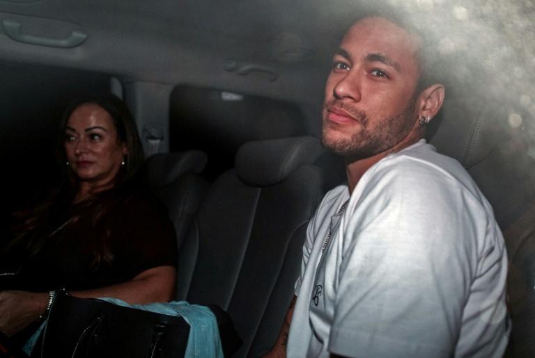 La star du football Neymar (D) et sa mère Nadine Goncalves Da Silva à leur arrivée à Belo Horizonte, au Brésil, le 2 mars 2018, où l'attaquant a été opéré du pied droit. Photo: AFP / NELSON ALMEIDA