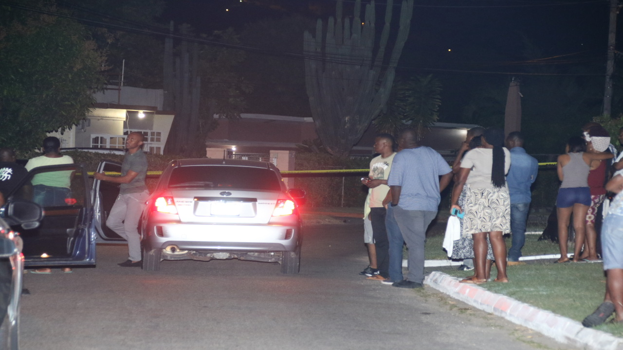 People gather at the crime scene in Havendale, St Andrew where a motor vehicle examiner was shot and killed on Thursday night.