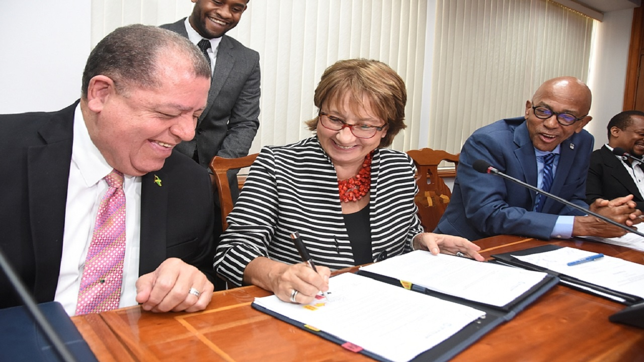 Galina Sotirova (centre), Country Manager, World Bank, signs the US$15,000 loan for the Access to Finance For Micro, Small and Medium Enterprises (MSMEs) Project witnessed by Audley Shaw, (left) Minister of Finance and the Public Service and Milverton Reynolds, Managing Director, Development Bank of Jamaica.