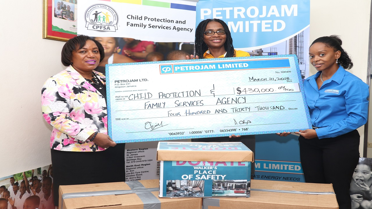 (L-R) CEO of Child Protection and Family Services Agency Rosalee  Gage-Grey  Judith Jaggon, President, Petrojam's Community Outreach Committee and Latoya Pennant, Public Relations Officer smiles for the camera with the donation cheque at the handing over ceremony last Thursday at the  Child Protection and Family Services Agency.