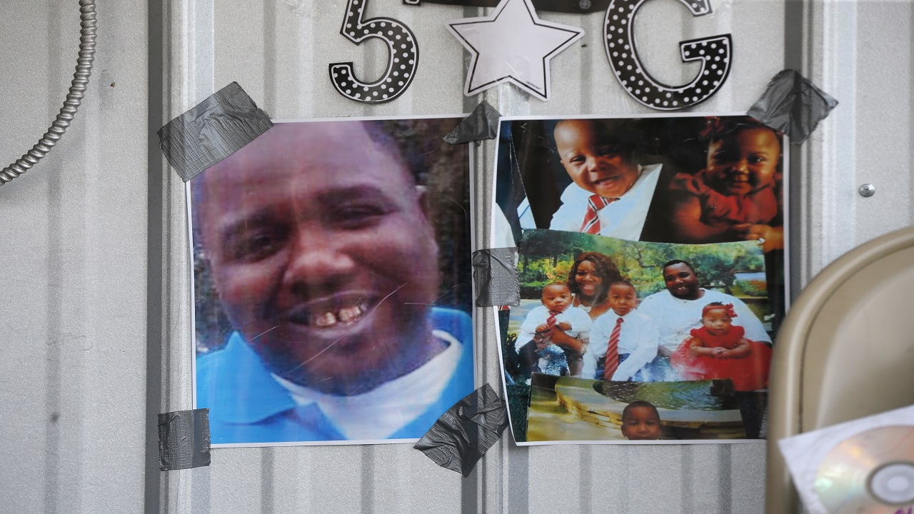 FILE - In this July 6, 2016 file photo, photos of Alton Sterling are taped to the wall at a makeshift memorial outside the Triple S convenience store in Baton Rouge, La. Sterling, was shot and killed outside the store where he was selling CDs by Baton Rouge police. On Tuesday, March 27, 2018, Louisiana's attorney general ruled out criminal charges against two white Baton Rouge police officers in the fatal shooting of Sterling. (AP Photo/Gerald Herbert, File)