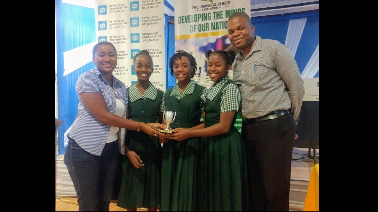 Listra Clemetson, the Jamaica Chess Federation Women's Chess Chairperson, poses with the winning St. Jago High School Team, (from left to right) Woman Candidate Master, Adani Clarke, Johmoi Blake and Jeshana Vincent as well as their coach, National Master Mikhail Solomon.