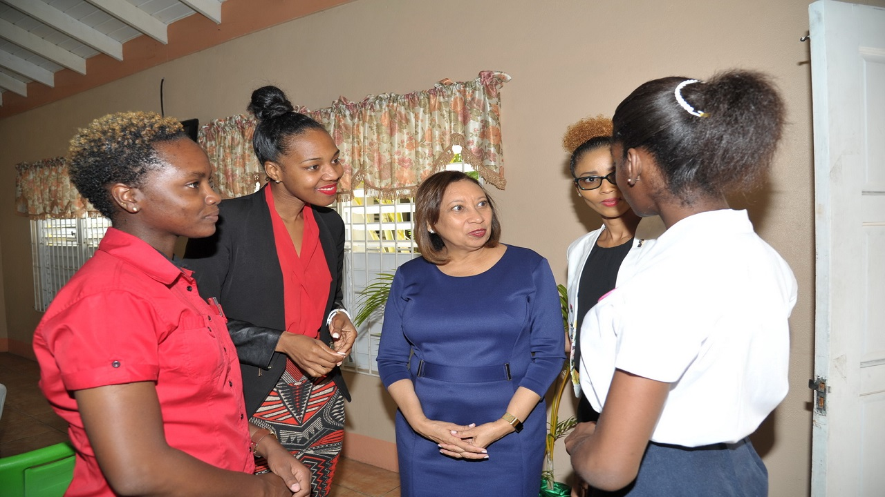 From left to right: Panellists, Abigail Henry, Terri-Karelle Reid, Camille Facey and president elect of Kiwanis Club of Young Professionals Kingston, Jamaica, Naketa West listens attentively as one of the adolescent mothers, Karesha, shares her dreams at the recently held panel discussion organized by club at the Women's Centre Foundation of Jamaica.