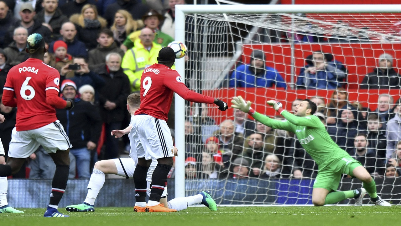 Manchester United's Romelu Lukaku, centre, watches the ball as he scores his side's first goal of the game against Swansea, during their English Premier League football match at Old Trafford in Manchester, England, Saturday March 31, 2018.