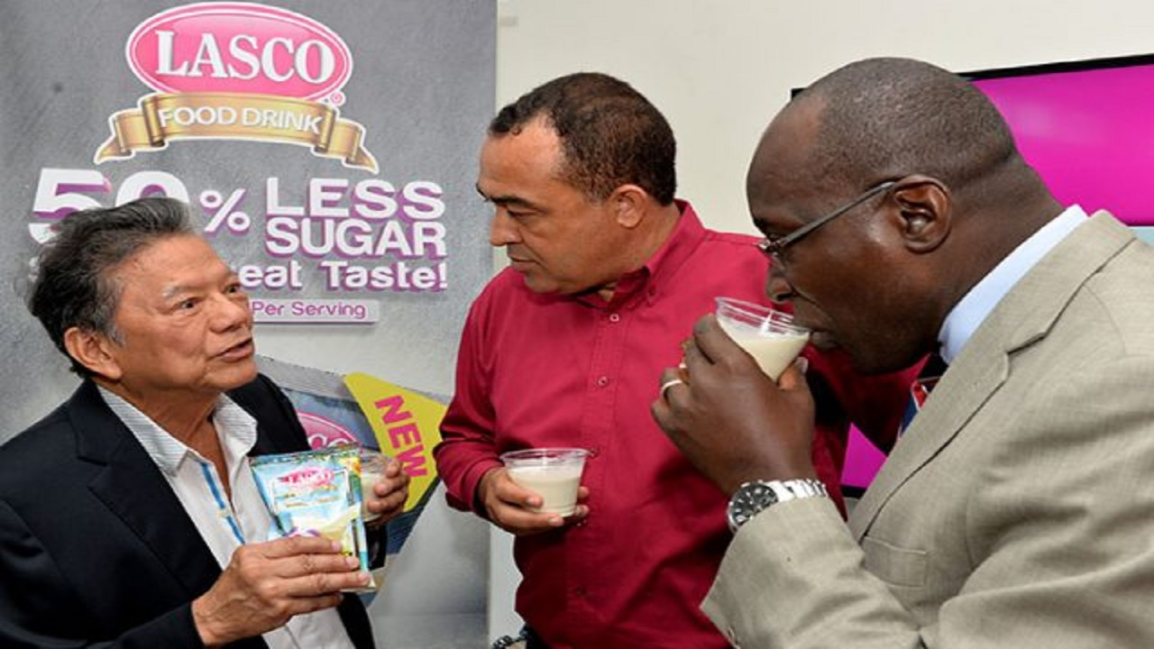 Minister of Health, Dr  Christopher Tufton (centre), listens as Executive Chairman of the LASCO Group of Companies, Lascelles Chin (left), provides details about the company's low-sugar food drinks, which were launched during a press conference at the company's Central Village plant in St Catherine on Wednesday.  Sharing in the moment, Education Minister Ruel Reid (right) samples a drink.