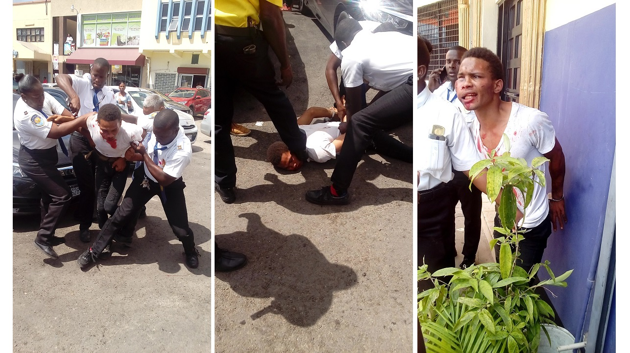 Photos show private security officers trying to subdue an alleged phone grabber at a plaza in Half-Way Tree.