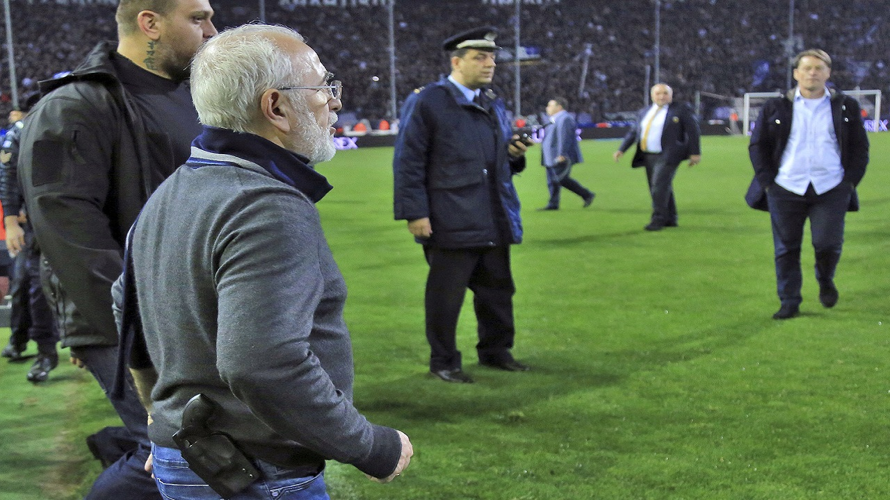 (Image: AP: PAOK owner Ivan Savvidis marches on to the pitch during the match on 11 March 2018)