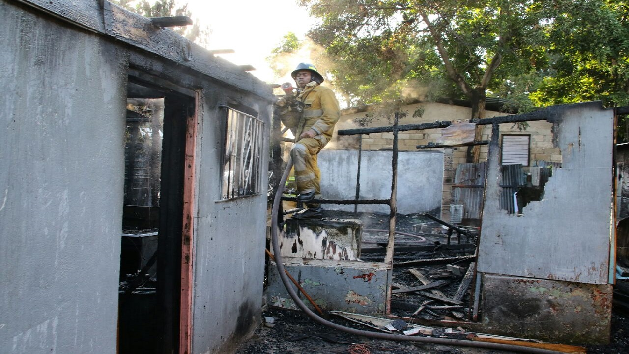 A firefighter attends to the house in Grants Pen, St Andrew that was gutted by fire on Thursday.