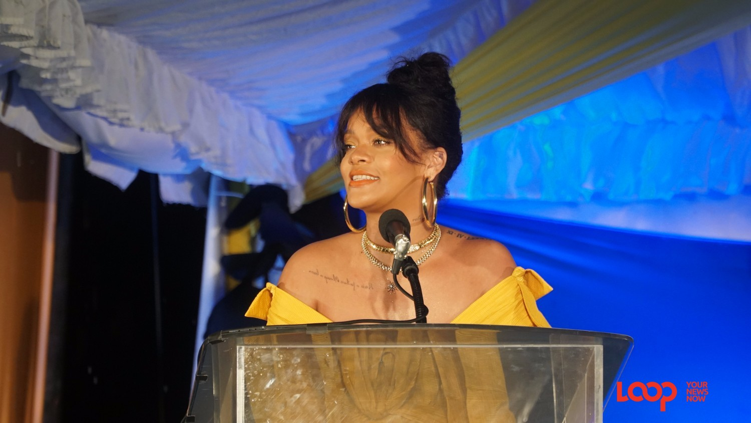 Rihanna speaking at the podium during the renaming ceremony at Rihanna Drive.