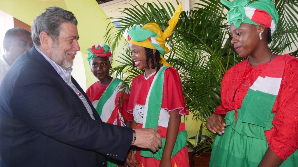 Premier Ralph Gonsalves van St. Vincent & the Grenadines wordt welkom geheten door dames in traditionele kleding.
