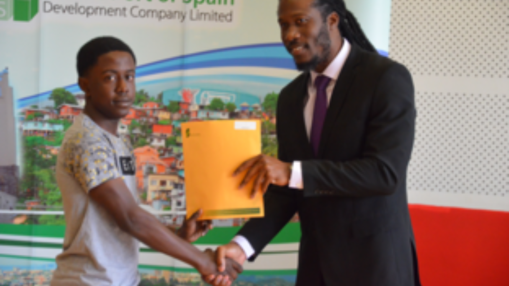 Adrian Leonce, Member of Parliament for Laventille East/Morvant presents a young graduate with his certificate.