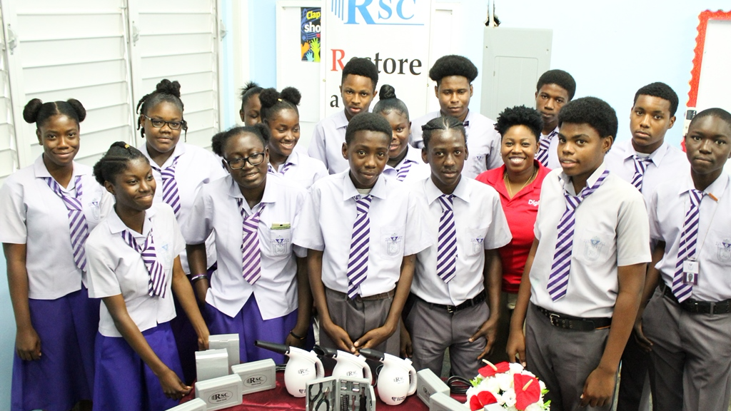 Students of the Roxborough Secondary School Tobago are all excited about the new Tech, which forms part of the Digital Citizenship Programme.  With them is Cindyann Currency, Operations Manager, Digicel Foundation
