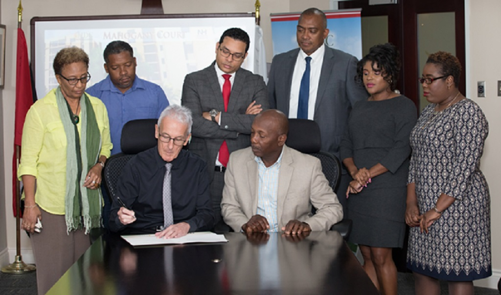 NH International (Caribbean) Ltd Managing Director, John Connon, signs contract with HDC. Seated next to him is HDC Chairman Newman George. 