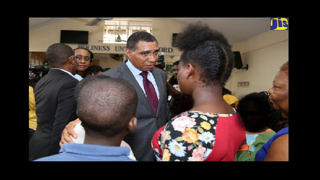 Prime Minister Andrew Holness offers words of comfort to wards of  Walker's Place of Safety at Lyndhurst Crescent in Kingston, following an early morning fire in January of this year. (File photo via Jamaica Information Service)