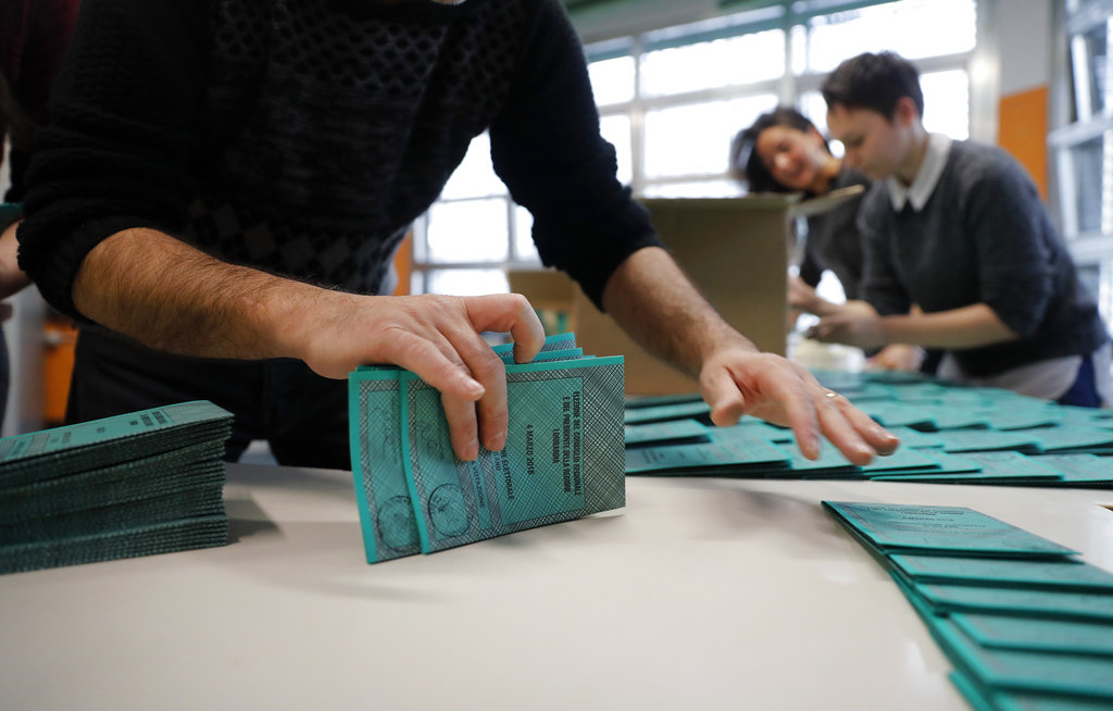 Polling station workers prepare ballots in Rozzano, near Milan, Italy. (AP Photo/Antonio Calanni)
