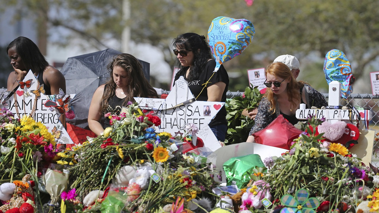 (Image: AP: Mourners place flowers at Marjory Stoneman Douglas High School on 25 February 2018)