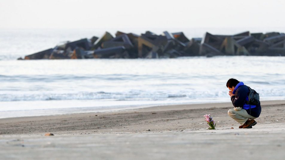 A man prays after offering flowers in Arahama coastal area where the tsunami struck in 2011, in Sendai city, northern Japan, Sunday, March 11, 2018. (Yusuke Ogata/Kyodo News via AP)