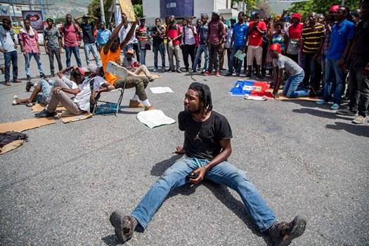 Un étudiant assis en pleine rue lors d'une manifestation en 2017. Photo : LoopHaiti