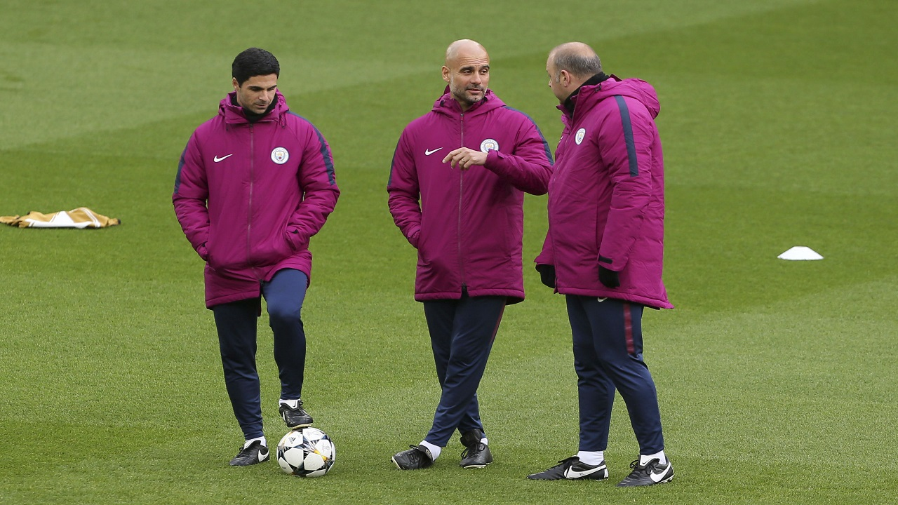 Manchester City manager Pep Guardiola, centre, speaks to his coaching staff during a training session at Anfield in Liverpool, England, Tuesday April 3, 2018.