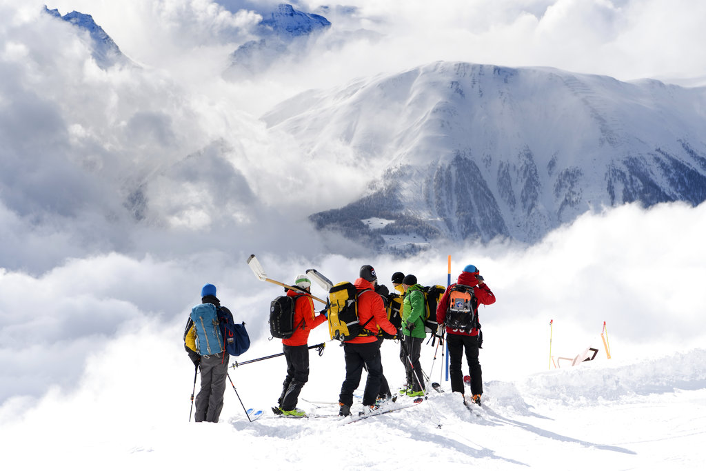 Rescuers stand near an avalanche site near Fiesch, Switzerland, Sunday. (Jean-Christophe Bott/Keystone via AP)