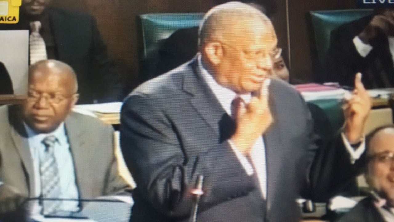 Opposition Leader Dr Peter Phillips shows two fingers in Parliament on Wednesday.
