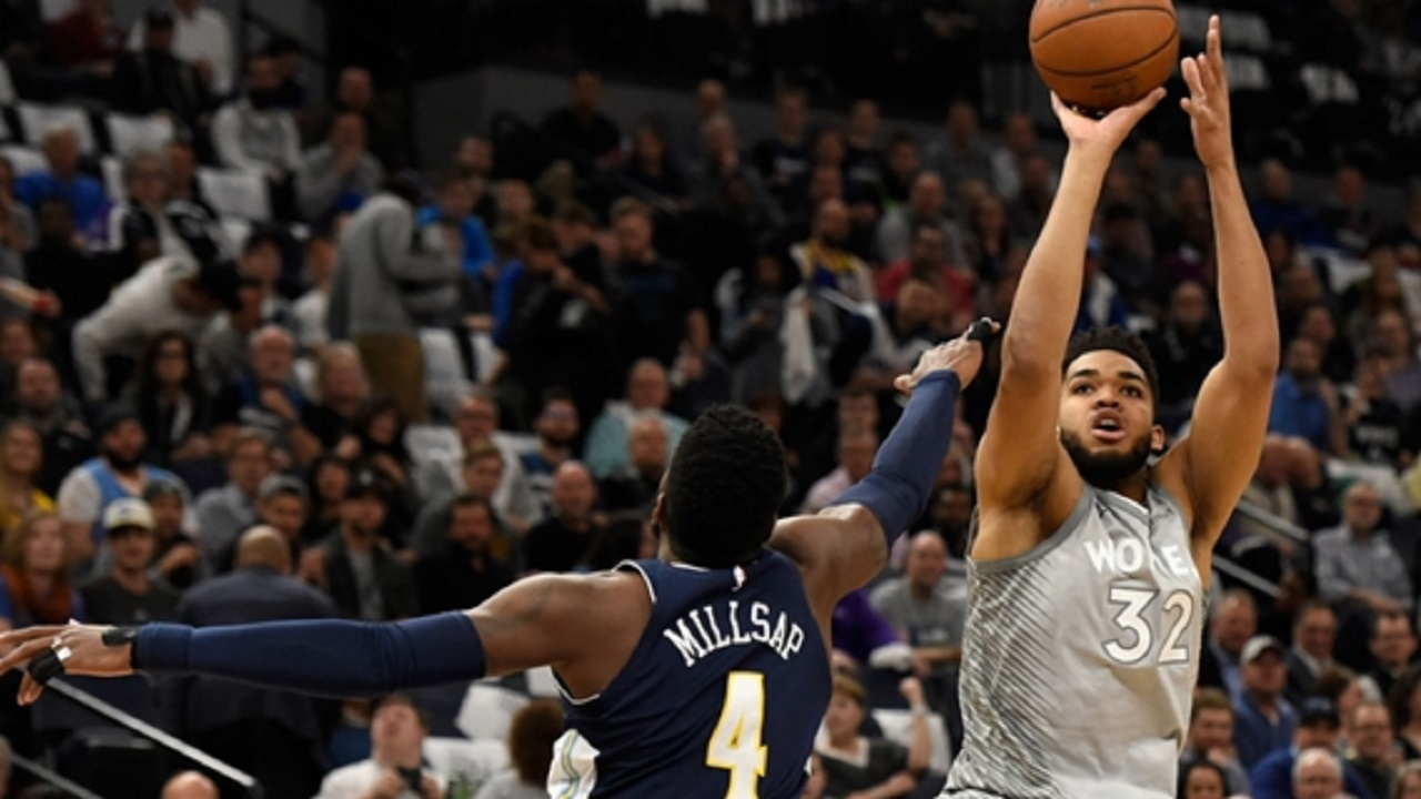 Karl-Anthony Towns shoots the ball over Paul Millsap.