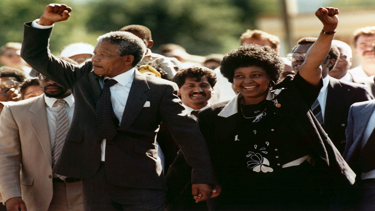 In this file photo dated Sunday, February 11, 1990, Nelson Mandela and wife Winnie, walk hand in hand, raising their clenched fists upon his release from Victor prison, Cape Town, 27 years in detention. South African state broadcaster SABC said Monday April 2, 2018, that anti-apartheid activist Winnie Madikizela-Mandela has died. (AP Photo)