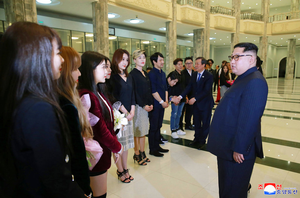In this photo provided by the North Korean government, North Korean leader Kim Jong Un, right, talks to members of the South Korean artistic group, including the South's pop legends and popular girl band Red Velvet, after their performance in East Pyongyang Grand Theater in Pyongyang, North Korea. (Korean Central News Agency/Korea News Service via AP)