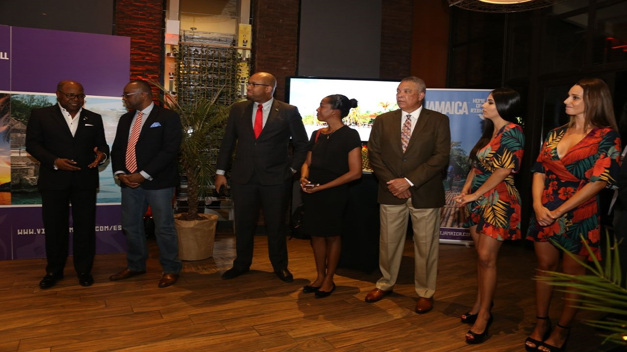 Tourism Minister, Edmund Bartlett (left) conversing with Donovan White, Director of Tourism, at a reception for Chile's travel industry hosted by the JTB in Santiago, Chile. Joining them are (left to right): Delano Seiveright, Senior Advisor/Strategist, Ministry of Tourism; Fiona Fennell, Director of Communications, Ministry of Tourism; Donnie Dawson, Deputy Director of Tourism, Sales/USA and Latin America; and two Chilean hostesses for the Jamaica reception.